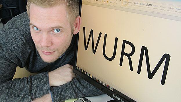Moderator hält sein Ohr an den Bildschirm. Darauf steht Wurm.