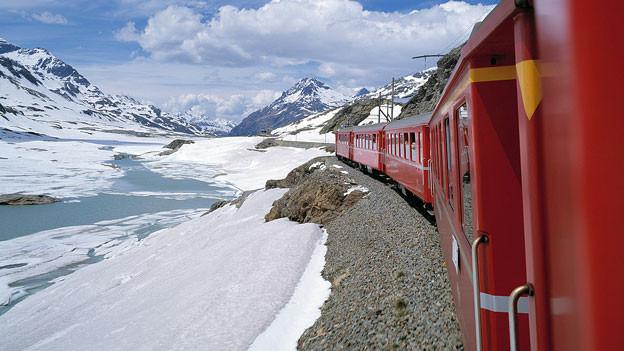 Ein roter Zug in schneebedeckter Landschaft.