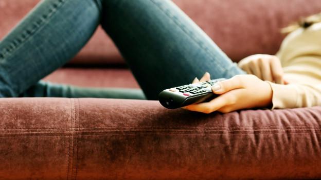 Frau mit Fernbedienung auf Couch.