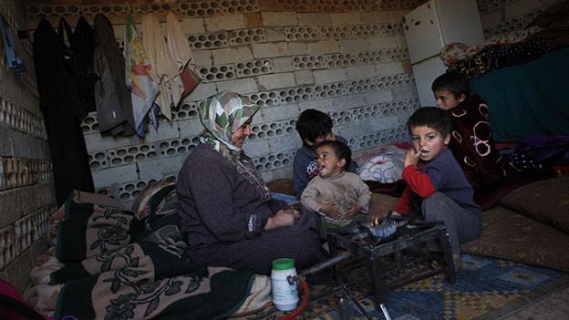-frau mit Kopftuch mit vier Kindern am Boden ihrer Baracke.