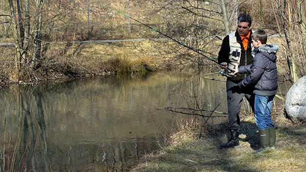 Mann zeigt einem Jungen, wie man fischt. sie stehen an einem Fluss.