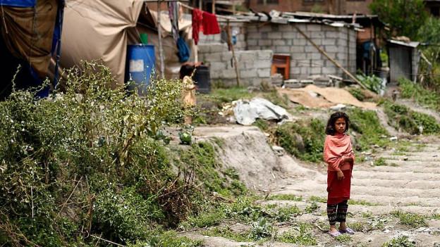 Mädchen steht in Bhaktapur auf der Strasse.