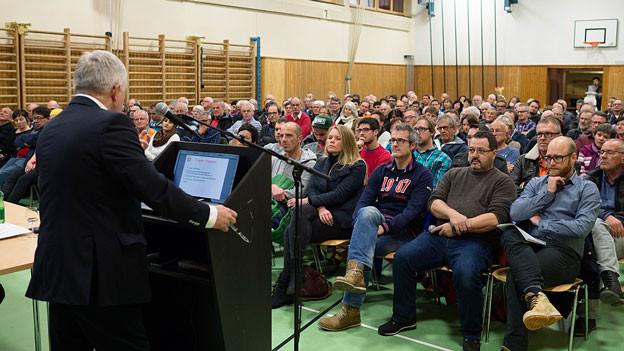 Ein Mann steht in einer Turnhalle am Rednerpult und spricht zu rund 200 Leuten.