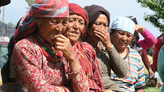 Ältere Frauen warten in einer Reihe.