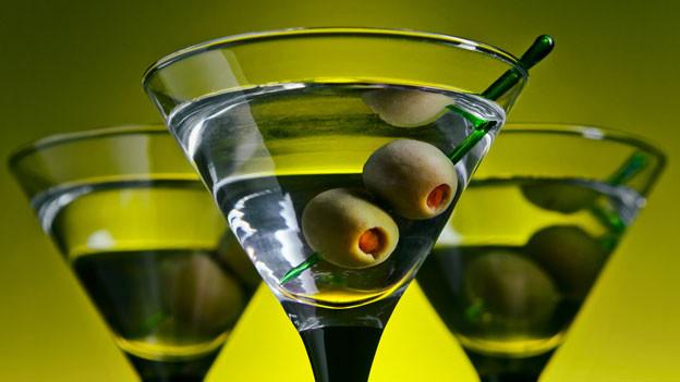 Drei Gläser mit Wermut und Oliven drin.