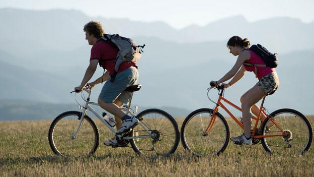 Zwei Personen auf dem Mountainbike.