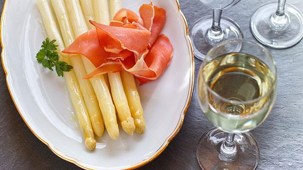 Weisse Spargeln mit einem Glas Weisswein.