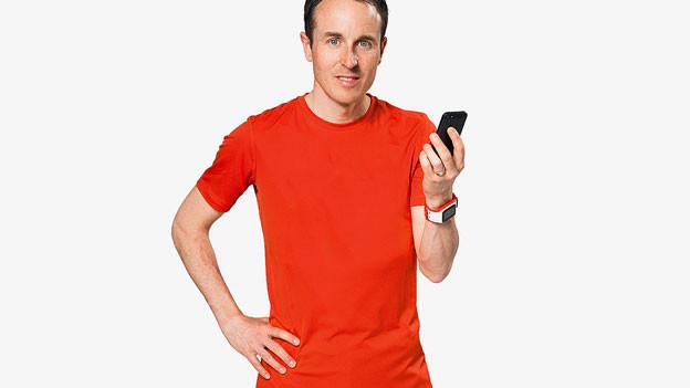 Viktor Röthlin posiert mit einem Handy in der Hand.