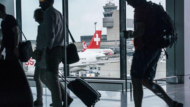 Flugpassagiere laufen mit Handgepäck durch einen Gang im Flughafen Zürich.