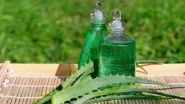 Kosmetikflasche aus Glas - daneben liegen Aloe Vera-Blätter.