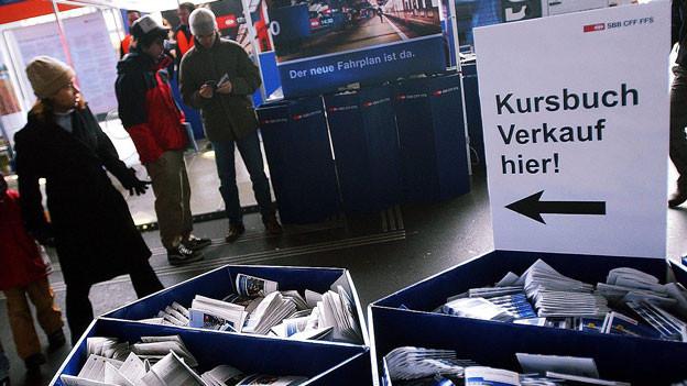 Menschen stehen bei Kisten mit Fahrplänen und auf einem Schild steht: «Kursbuchverkauf hier!»