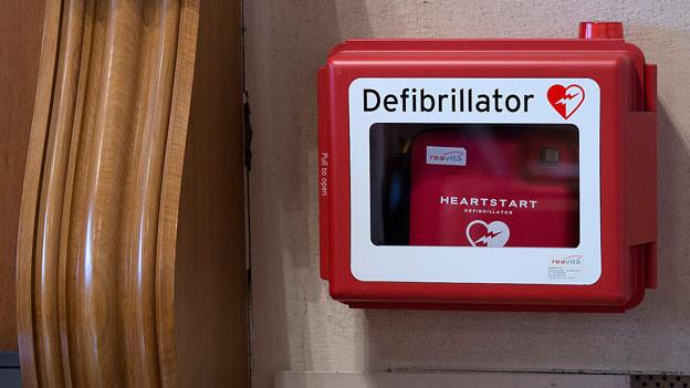 Ein Defibrillator hängt an einer Wand.
