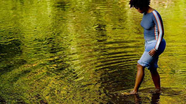 Eine Frau geht barfuss im seichten Wasser.