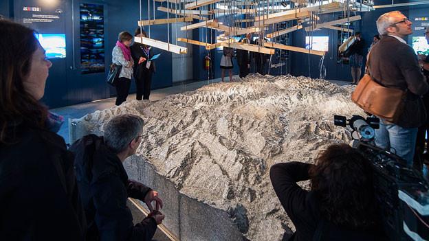 Besucher stehen bei einem Alpen-Relief.