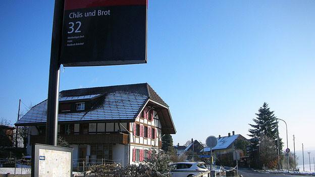 Busstationsschild von «Chäs und Brot», im Hintergrund ein Bauernhaus im Winter.