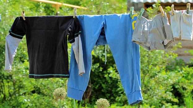 Hosen und Unterhosen hängen an einer Wäscheleine.