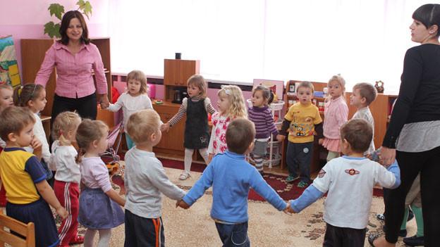 Kinder im Kindergarten stehen im Kreis und geben sich die Hand.