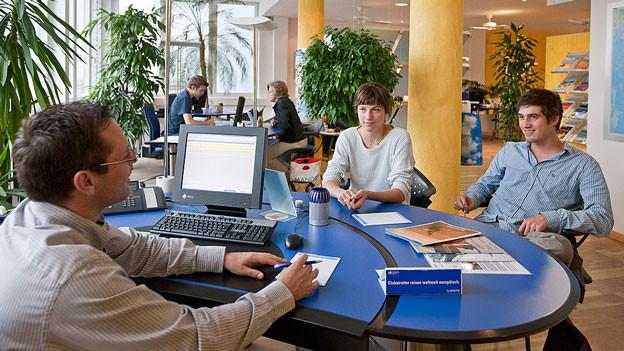 Zwei Personen lassen sich im Reisebüro beraten.