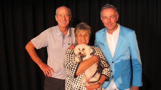 V.l.n.r.: Walter Zibung, Marlène Wirthner-Durrer mit Hund und Dani Fohrler posieren vor einem schwarzen Vorhang.