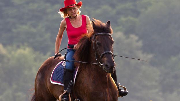 Eine Frau mit Cowboy-Hut auf dem Pferd.