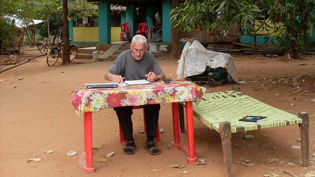 Erwin Eigenmann sitzt draussen an einem Tisch.