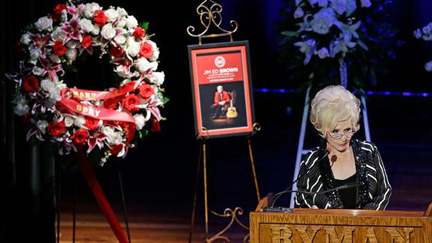 Brenda Lee hält an der Beerdigung von Jim Ed Brown eine Ansprache. Im Hintergrund steht ein Kranz mit weissen, roten und rosaroten Blumen.