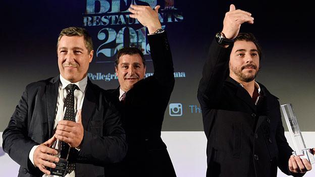 Drei jubelnde Männer auf einer Bühne.
