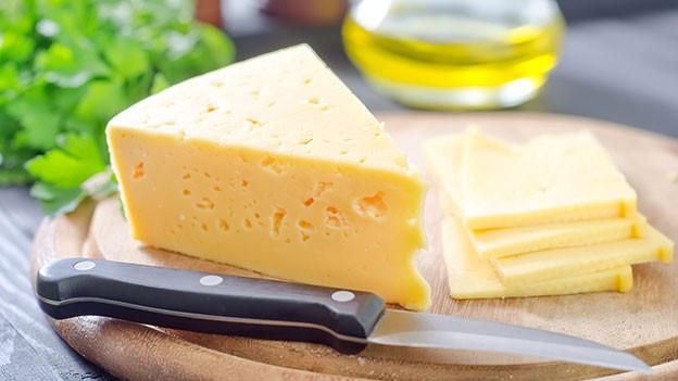 Holzbrett und Messer mit einem Stück Käse darauf.
