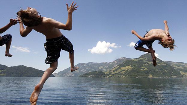 Kinder springen in den See.