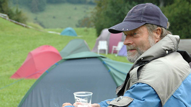 Mann steht auf einer Wiese mit Zelten.