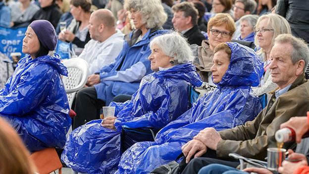 Open Air Besucher mit Regenschutz.