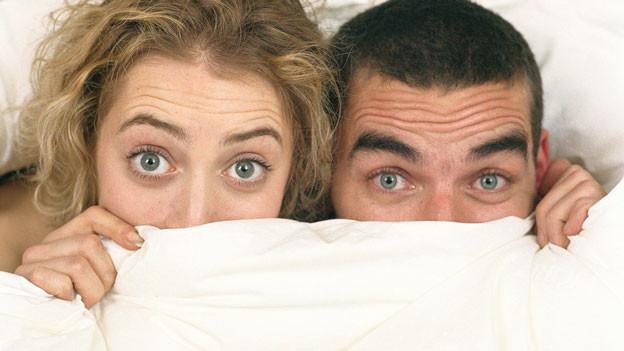Eine Frau und ein Mann schauen überrascht unter einer Bettdecke hervor.