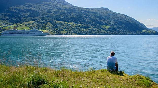 Mann sitzt am Ufer und schaut auf ein Kreuzfahrtschiff.
