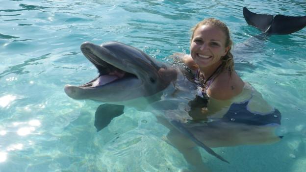 Frau mit Delfin in einem Schwimmbecken.