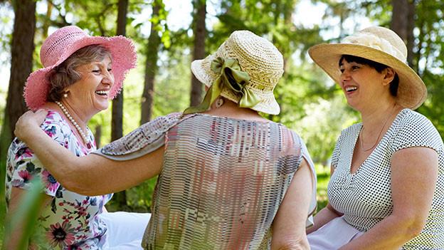 Drei Frauen mit Hut quatschen miteinander.