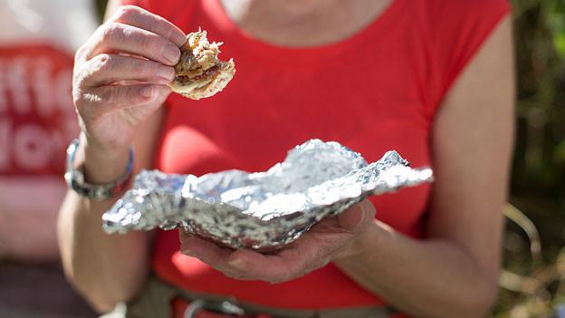 Eine Person isst eine Speise, die sie in Alufolie eingepackt hatte.