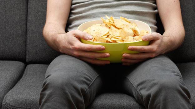 Ein Mann sitzt auf dem Sofa und isst Pommes Chips.