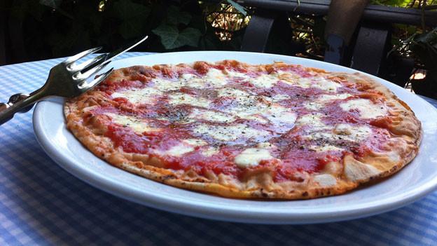 Pizza auf einem Gartentisch.