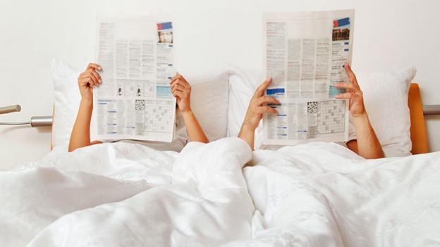 Ehepaar im Bett. Beide lesen Zeitung.