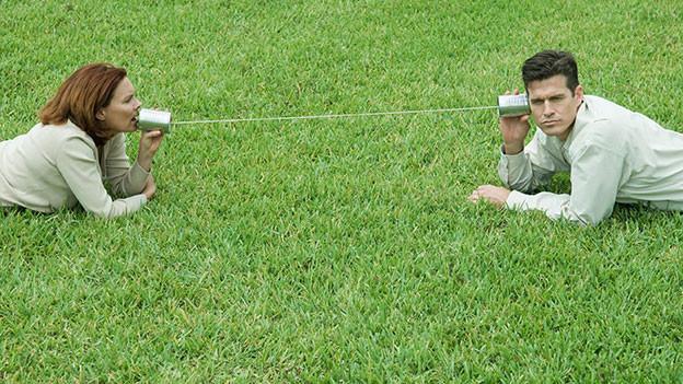 Ein Paar liegt weit auseinander auf dem Rasen. Zwischen ihnen ist eine Schnur und an den jeweiligen Enden Büchsen. Der eine spricht rein, der Andere horcht.