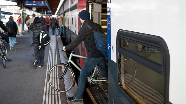 Ein Mann steigt mit seinem Velo aus dem Zug.
