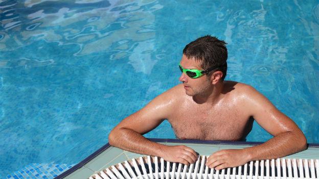 Mann mit Schwimmbrille steht im Pool