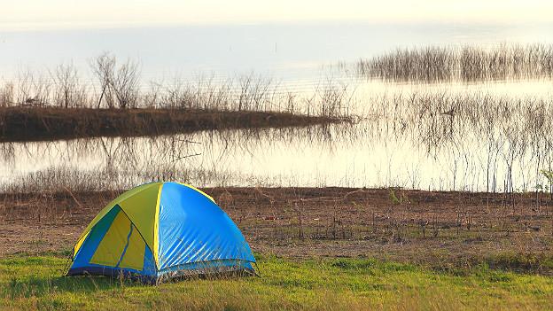 Kleines Zelt im Gras vor See
