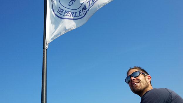 Mann auf dem Boot mit weiss-blauer Fahne.
