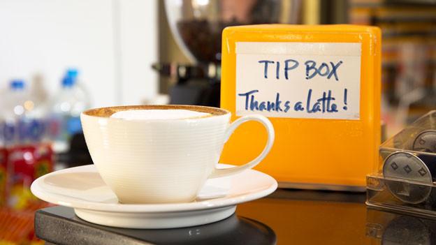 Neben einer Kaffeetasse steht eine kleine gelbe Kasse, auf der ein Zettel zum Trinkgeld-Geben animiert.