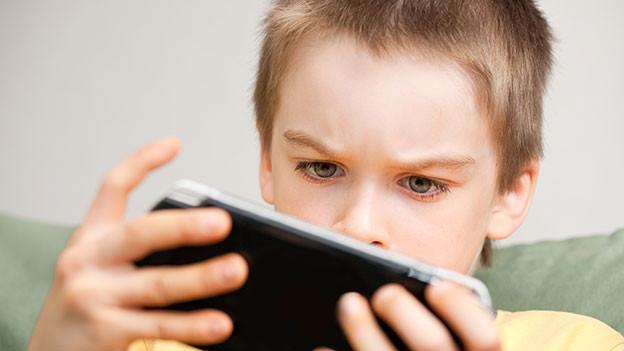 Kind hält ein Smartphone in den Händen und blickt darauf.