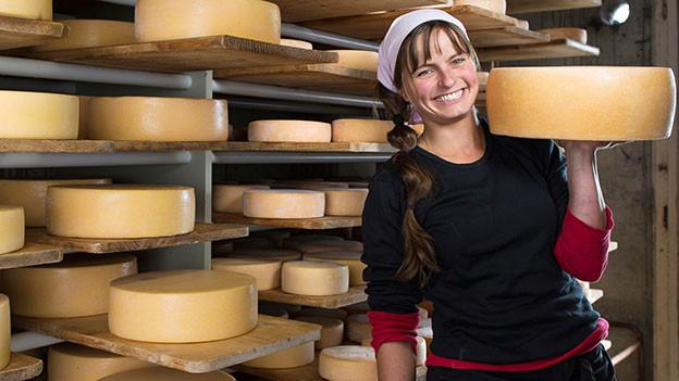 Frau mit Kopftuch stemmt im Käsekeller einen Käselaib in die Höhe.