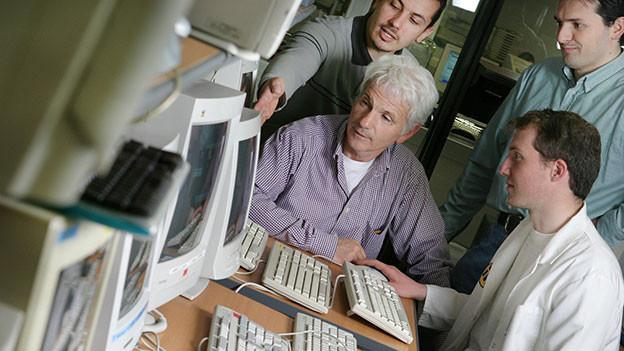 Älterer Mann sitzt mit Jungen am Computer und gibt sein Wissen weiter.