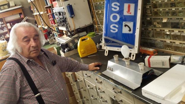 Der Erfinder Jürg Nigg steht in seiner Werkstatt vor einem Modell einer Tunnel-Beleuchtung und einer Testlampe