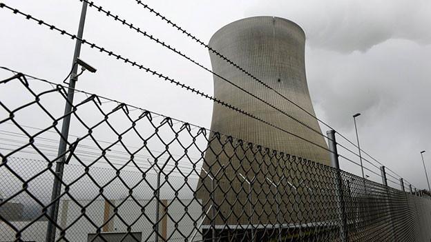 Der Kühlturm vom Kernkraftwerk Leibstadt mit Stacheldraht im Vordergrund.
